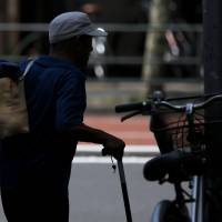 An unemployed elderly man carries his clothes to a laundromat in Tokyo, on July 8, 2013. | BLOOMBERG