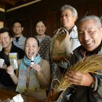 Rina Sakai (front row, center), smiles alongside local rice and egg producers in Oshu, Iwate Prefecture, on Nov.5. | KYODO
