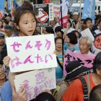 A girl's message reads 'No war' during a Tokyo rally on July 1 opposing reinterpretation of the Constitution over collective self-defense. | KYODO