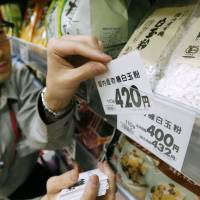 An employee at an Aeon store in Mihama Ward, Chiba, changes a price tag March 31 to reflect the hike in the consumption tax that took effect the next day. | KYODO