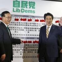 Prime Minister Shinzo Abe is all smiles after a flower indicating victory is placed above his name on the candidates board at Liberal Democratic Party headquarters in Tokyo on the night of the Lower House election Dec. 14. | KYODO