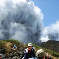 Hikers make their way down Mount Ontake as the volcano erupts on Sept. 27. | KYODO