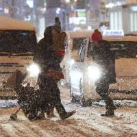 Pedestrians cross a street in Sapporo during a snow storm on Monday. | KYODO