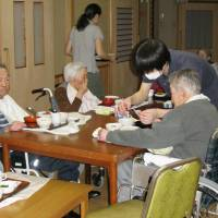 Old and young: Residents at an old-age home are served a meal at dinnertime. | KYODO