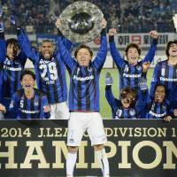 As good as it gets: Gamba Osaka captain Yasuhito Endo holds the J. League championship hardware and celebrates with his teammates after Saturday's season finale. | KYODO