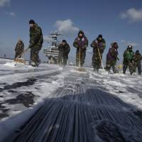 Risky business?: U.S. Navy crew members clean the flight deck to remove radiation from the USS Ronald Reagan aircraft carrier on March 23, 2011. | AP