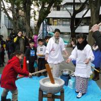 Making mochi: During the annual o-mochitsuki festivities, a Nishimachi student gets to pound rice with her father, a member of the Japanese teaching staff. | COURTESY OF NISHIMACHI INTERNATIONAL SCHOOL