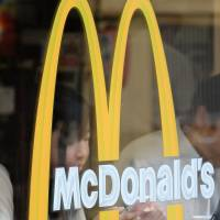 Customers sit behind a logo at a McDonald's restaurant in Tokyo in July.   BLOOMBERG