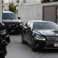 A Jordanian police stands guard as vehicles, part of a convoy carrying Japanese envoy, State Minister for Foreign Affairs Yasuhide Nakayama, leave the Japanese Embassy in Amman Saturday.  | REUTERS