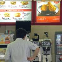 A man waits to place his order at a McDonald's in Tokyo. The fast-food chain has recently been hit with a series of incidents in which foreign objects have been found by customers in chicken nuggets sold in Japan. | BLOOMBERG