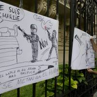 An Argentine cartoonist draws at the gates of the French Embassy in Buenos Aires on January 7, 2015, during a demonstration against the attack by unknown gunmen in the offices of the satirical weekly Charlie Hebdo in Paris.   | AFP-JIJI
