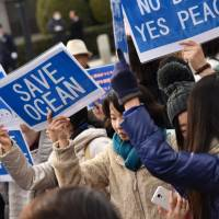 Protesters against the new U.S. Marine base planned for Henoko Bay in Nago, Okinawa, hold placards outside the Diet on Sunday. | FINBAR O'MALLON