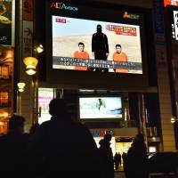 People look at a large TV screen near Shinjuku Station in Tokyo on Jan. 20, showing news reports about two Japanese men who have been kidnapped by the Islamic State group. | AFP-JIJI