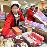 Employees of a department store place products into 'lucky bags' for their new year sale in Tokyo on Dec. 26. | AFP-JIJI