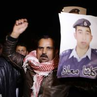 People from the al-Kaseasbeh tribe and other tribes take part in a demonstration outside of Jordan's cabinet in Amman Tuesday calling for the release of Jordanian pilot Lt. Mu'ath al-Kaseasbeh. | AP