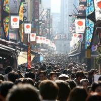 Shoppers walk through the Ameya Yokocho shopping district in Tokyo in late December. Inflation slowed more than expected in the month, adding to Bank of Japan Gov. Haruhiko Kuroda's challenges in reflating the economy.   BLOOMBERG
