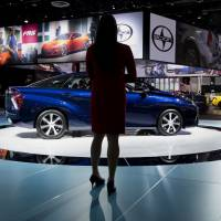 A woman stands next to Toyota's new Mirai fuel cell vehicle at the 2015 North American International Auto Show in Detroit on Jan. 13. | BLOOMBERG