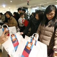 A tourist from Hong Kong (right) joins a crowd of shoppers grabbing 'fukubukuro' (lucky bags) at the Mitsukoshi department store in Tokyo's Ginza district on Jan. 2. | KYODO