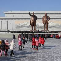 North Koreans gather at Mansu Hill, which features statues of the late leaders Kim Il Sung and Kim Jong Il, in Pyongyang on Dec. 16. | AP