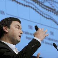 French economist Thomas Piketty, author of the best-seller 'Capital in the Twenty-First Century,' addresses a symposium in Paris earlier this month. He is visiting Japan to oversee the release of the book's Japanese version. | AFP