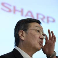 Sharp Corp. President Kozo Takahashi addresses reporters in Tokyo in May. The struggling electronics-maker said it may revise downward its profit forecasts for the current business year due to a worsening business environment.   BLOOMBERG