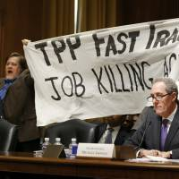 A policewoman removes a man protesting the Trans-Pacific Partnership as U.S. Trade Representative Michael Froman (right) testifies at a Senate Finance Committee hearing in Washington on Tuesday. | REUTERS