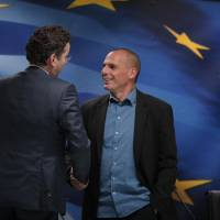 Dutch Finance Minister and Eurogroup President Jeroen Dijsselbloem (left) talks to Greek Finance Minister Yanis Varoufakis as he leaves following a joint news conference after their meeting at the Finance Ministry in Athens on Friday. | AP