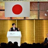 Prime Minister Shinzo Abe delivers a speech at a New Year's party in Tokyo on Tuesday. Listening to him are (seated, left to right) Keidanren Chairman Sadayuki Sakakibara, Keizai Doyukai (Japan Association of Corporate Executives) Chairman Yasuchika Hasegawa and Japan Chambers of Commerce Chairman Akio Mimura. The three business groups hosted the annual party. | AFP-JIJI