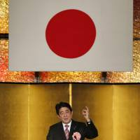 Prime Minister Shinzo Abe addresses a New Year's party hosted by business lobbies in Tokyo on Tuesday. | REUTERS