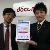 Kenji Nakayama (left), manager of Wi-Fi business at Docomo's M2M Business Department, and team member Satoshi Tsuruike demonstrate the Docomo Wi-Fi website for foreign visitors at the firm's headquarters in Tokyo.  | KAZUAKI NAGATA