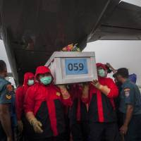 Indonesian rescue personnel unload a coffin bearing a body recovered from the underwater wreckage of AirAsia Flight QZ8501 from a military plane on arrival at Surabaya on eastern Java island on Friday, when divers finally managed to enter the submerged fuselage. | AFP-JIJI