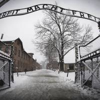 A woman walks through snow on Sunday near the entrance to the former Nazi concentration camp Auschwitz-Birkenau with the lettering 'Arbeit macht frei' (Work makes you free) in Oswiecim, Poland, days before the 70th anniversary of the liberation of the camp by Russian forces. | AFP-JIJI