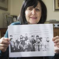 Marta Wise holds a photo taken by the Russian liberators of Auschwitz, showing her, (center), with about a dozen children in rags standing behind a row of barbed wire that has become one of the most iconic images of the Holocaust. | AP
