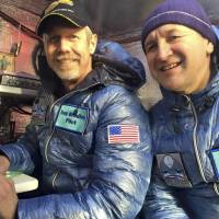 Pilots Troy Bradley of the U.S. and Leonid Tiukhtayev of Russia sit in the capsule of the Two Eagles balloon before setting off on their attempt to cross the Pacific and set a new distance and duration record for gas balloon travel in Saga Prefecture on Sunday. They have likened their trip so far to camping in the sky. | REUTERS