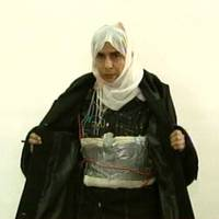 Iraqi Sajida al-Rishawi, appearing Nov. 13, 2005, opens her jacket and shows an explosive belt as she confesses on Jordanian state-run television to her failed bid to set off an explosives belt  inside one of three Amman hotels targeted by al-Qaida. Al-Rishawi, was sentenced to death. She has emerged as a potential bargaining chip in negotiations to secure the release of Japanese hostage Kenji Goto, who is being held by the Islamic State group, the successor of al-Qaida in Iraq. | AP