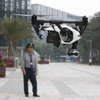 A security guard watches a demonstration of a DJI Technology Co. Inspire 1 drone in the city of Shenzhen, southern China, on Dec. 15. Founded in 2009, DJI has become the leading supplier in the fast-growing market for civilian drones — possibly the first Chinese brand to achieve No. 1 status in a global consumer product. | AP
