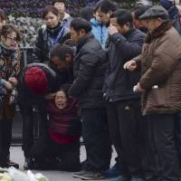 A grieving woman is comforted by other relatives of a New Year's Eve stampede victim on Tuesday at the site of the tragedy in Shanghai. | AP