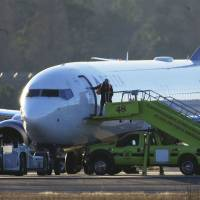 A worker closes the door to a Delta Airlines airplane sitting on the tarmac at Hartsfield-Jackson Atlanta International Airport in Atlanta on Saturday. Police searched the Delta airplane and a Southwest airplane at Atlanta's main airport after authorities received what they described as 'credible' bomb threats. | AP