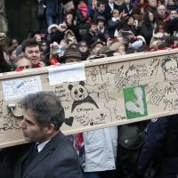Cartoons and tears at funerals of Charlie Hebdo victims