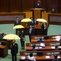 Pro-democracy lawmakers hold yellow umbrellas — the symbol of the Occupy Central movement — as Chief Executive Leung Chun-ying (center) delivers his annual policy address at the Legislative Council in Hong Kong on Wednesday. | REUTERS