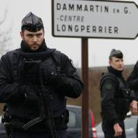 Armed police officers take up positions near the scene of a hostage-taking at an industrial zone in Dammartin-en-Goele, northeast of Paris, on Friday. | REUTERS