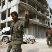 A fighter with the Kurdish People's Protection Units flashes a victory sign as he patrols the northern Syrian town of Kobani on Wednesday. | REUTERS