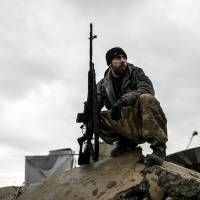 A Kurdish sniper sits in the rubble of the Syrian border town of Kobani on Saturday. Islamic State militants struck at Kurdish forces southwest of the Iraqi city of Kirkuk on Friday, killing a top peshmerga commander. | AFP