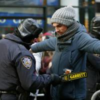 A police officer checks a man entering a cordoned off area on New Year's Eve in Times Square in New York. Security was especially tight this year in the wake of anti-police sentiment that resulted in the slaying of two New York city police officers last week. | AP