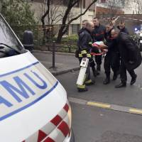 A victim is taken away on a stretcher on Wednesday after armed gunmen stormed the offices of the French satirical newspaper Charlie Hebdo in Paris, leaving at least 11 people dead.   AFP-JIJI