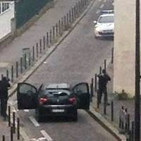 Armed gunmen face off against police near the offices of the French satirical newspaper Charlie Hebdo in Paris on Wednesday.