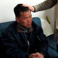 This image from a police video shows Kim Seong-baek meeting with his mother at the Guro police station in Seoul on Jan. 24, 2014, after he was rescued from a salt farm. | AP