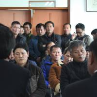 South Korean lawmakers (facing away from camera) meet with salt farm owners and workers as part of a human rights inspection on Sinui Island on Feb. 19, 2014. | AP