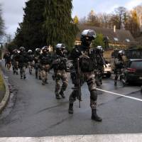 French police special forces patrol in Corcy, northern France, on Jan. 8 as part of a massive manhunt for the gunmen who shot dead 12 people in an Islamist attack at the Paris offices of the French satirical weekly Charlie Hebdo a day earlier. | AFP-JIJI