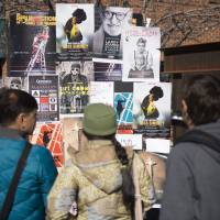 People gather around film posters on Main Street as the 2015 Sundance Film Festival kicked off on Thursday, in Park City, Utah. | AP
